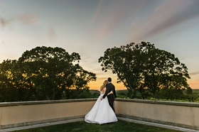 Wedding photo bride and groom looking at Sunset from balcony at Oheka Castle Angel Sanchez tuxedo