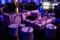 Plush furniture and ottomans with purple lighting