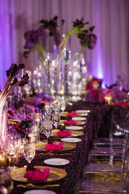 Wedding reception long table with purple texture tablecloth gold charger purple flowers pink napkins