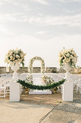 outdoor wedding ceremony old church white flowers greenery orchid colombia national flower