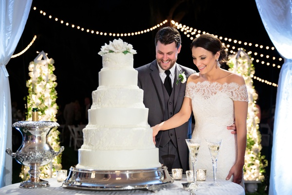 bride and groom cut six-tier wedding cake with lace detail