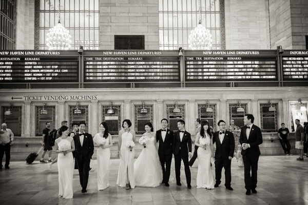 Black and white photo of bride and groom with bridesmaids and groomsmen at grand central station