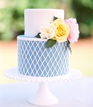 Wedding cake just for cutting blue and white diamond design on bottom fresh flowers on top fondant
