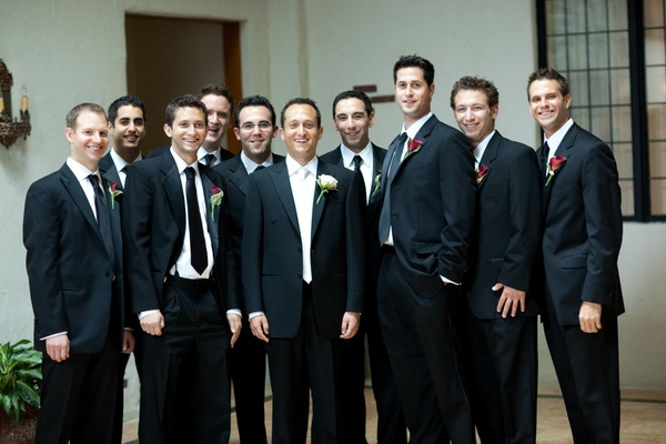 Groom with ten groomsmen in tuxedos and red boutonnieres