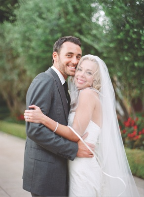 Simone Harouche, designer, in a Carolina Herrera gown embraces her groom in a grey Tom Ford suit