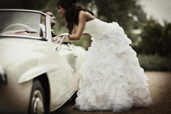 bride wearing dress with ruffled skirt and white classic car