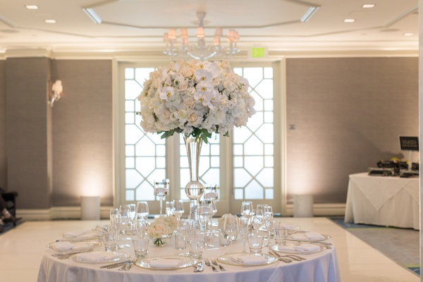 white wedding reception table with tall centerpiece, white dance floor