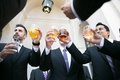 groomsmen in black tuxedos and blue or purple ties say cheers with drinks