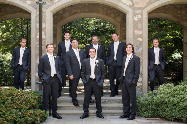 Groom and groomsmen in dark grey suits with white ties
