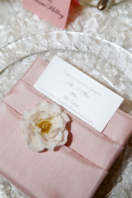 Clear charger plate on textured linen wedding reception single flower and menu tucked in