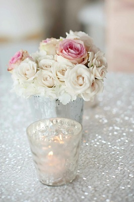 Small centerpiece of roses on white sequin tablecloth