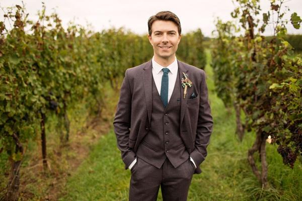 Nikita actor Noah Bean in three piece grey suit color tie in vineyard wedding reception ceremony