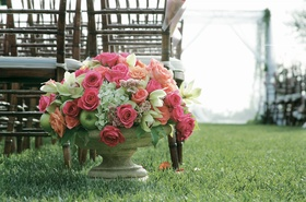 Stone vase filled with fruit and rose, hydrangea, and orchid flowers