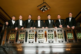 groom and groomsmen black white tuxedo bow tie on balcony in church classic ensembles