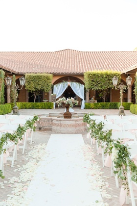 Wedding ceremony outdoor courtyard setting white aisle runner greenery pink ribbon apricot arch