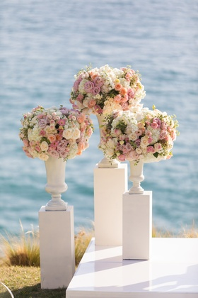 Three white pillars with vases full of white and pink flowers at wedding ceremony