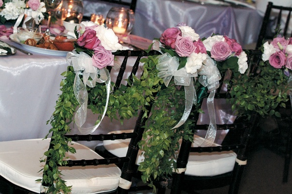 Reception chairs with green garlands and lavender roses
