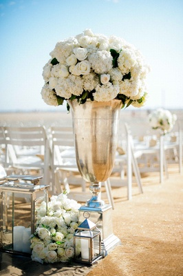 Beach wedding ceremony with tall silver urn, white roses, hydrangeas, lanterns