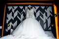 Wedding dress on white hanger embellished beaded bodice with full skirt on headboard