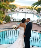 Bride and groom kiss above hotel pool