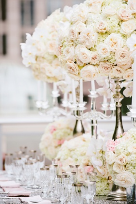 Wedding reception table with tall silver stands, low vases with white hydrangeas, orchids pink roses