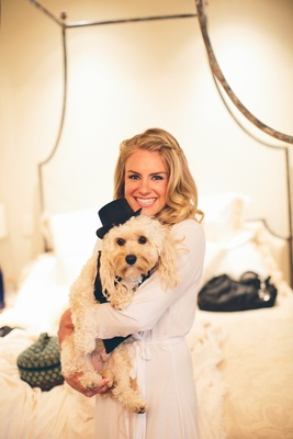 Bride holding puppy wearing tuxedo and hat