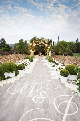 wedding ceremony outdoor grey wash wood aisle runner white initials monogram green boxwood hedge
