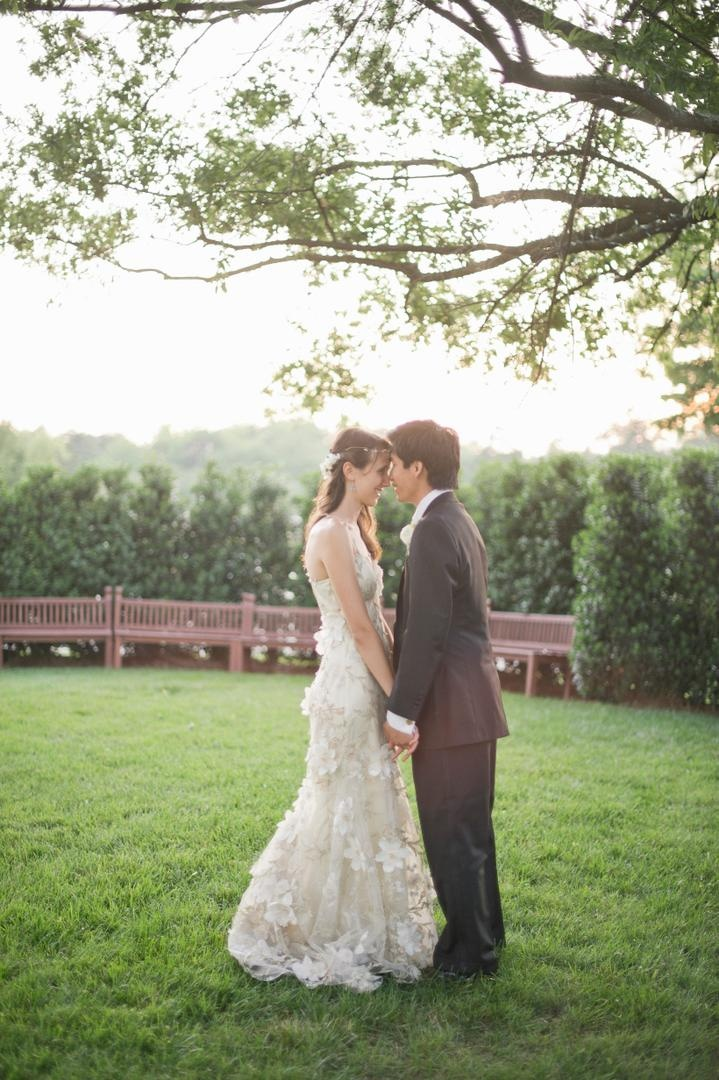 Bride with Asian American groom in grass park