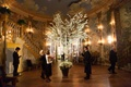 tree with greenery and white flowers indoors hanging white ribbons with escort cards