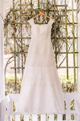 a beautiful lace wedding dress with four tiers and straps hangs up
