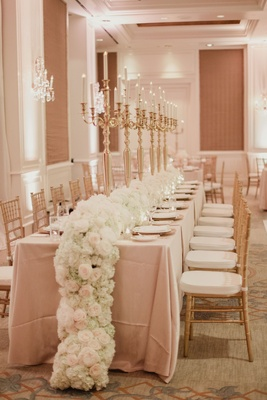 Wedding reception long table with white flowers cascading on floor gold candelabra on table