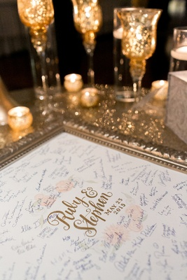 Wedding reception with a gold frame, bride and groom's name surrounded by flowers, guest signatures