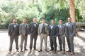 Groom in light grey suit with groomsmen in grey suits and bow ties brown shoes rustic wedding