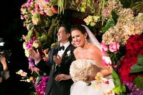 Bride in Vera Wang wedding dress holding round ivory bouquet under flower embellished chuppah