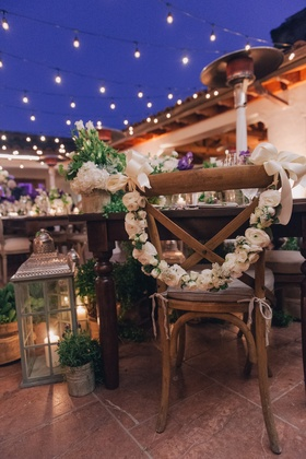 Wooden chair with white flower garland and ribbon