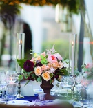 wedding reception with small floral arrangement with pink, burgundy & peach flowers between candles