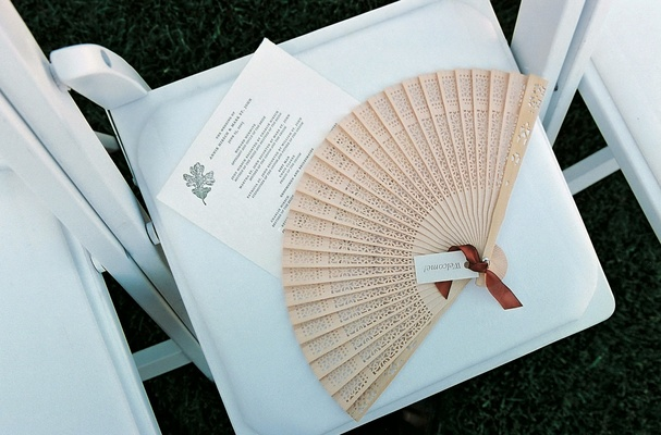 Wedding ceremony chair topped with fan and program