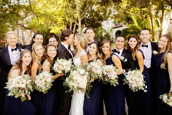 Bridesmaids in navy dresses and groomsmen in tuxedos at houston astros pitcher gerrit cole wedding
