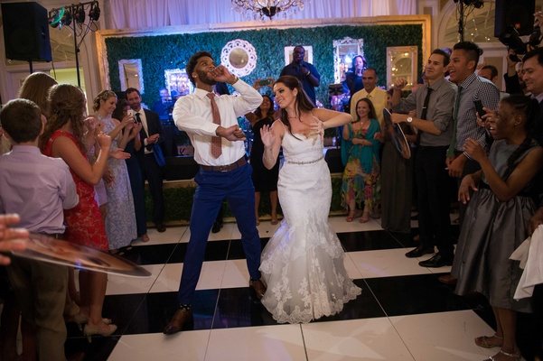 a newlywed couple dances down an aisle made by guests in the middle of dance floor