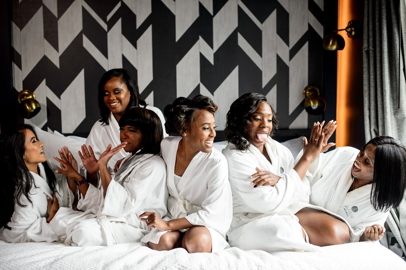 African American bride with bridesmaids on white hotel bed with robes bridal suite