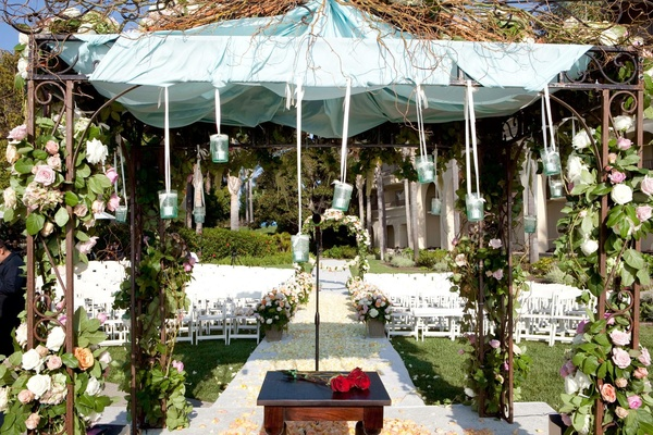 Altar beneath ceremony structure with garlands and flowers