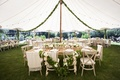 Dinner reception tent with wood tables and chairs