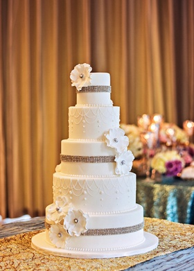Five layer white wedding cake with rhinestones and flowers
