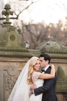 groom wearing a black tuxedo kisses his bride wearing a white gown with cap sleeves on the cheek