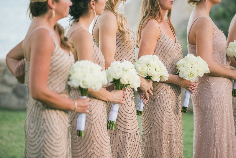bridesmaids holding simple white bouquets wearing champagne colored dresses silver embellishments