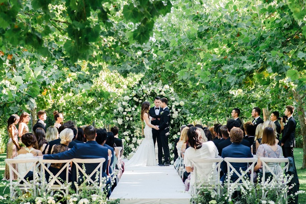 Vineyard guest chairs at outdoor ceremony among greenery trees white flowers white aisle runner