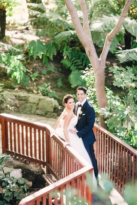 Bride in Vera Wang wedding dress and groom in blue tuxedo at Hotel Bel-Air bridge