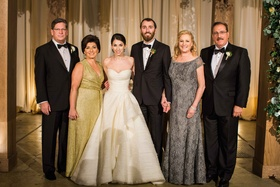 Mother of bride in v neck gold floor length gown and mother of groom in grey lace off shoulder dress