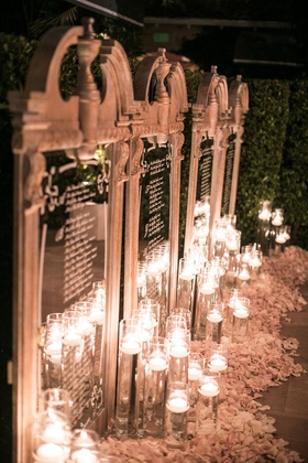 Wedding reception seating chart mirror illuminated with floating candles flower petals calligraphy