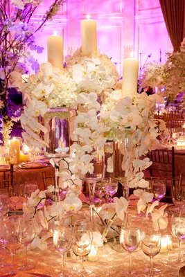 Wedding reception table with arrangements of white flowers and pillar candles